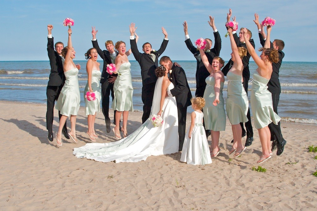 Bride and Groom taking their wedding day portraits with their Wedding Party on the Beach Jumping