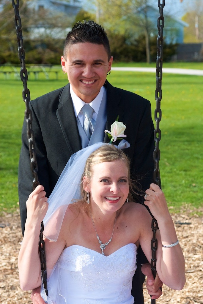 Groom and Bride in a Park on the Swings for their wedding day portraits