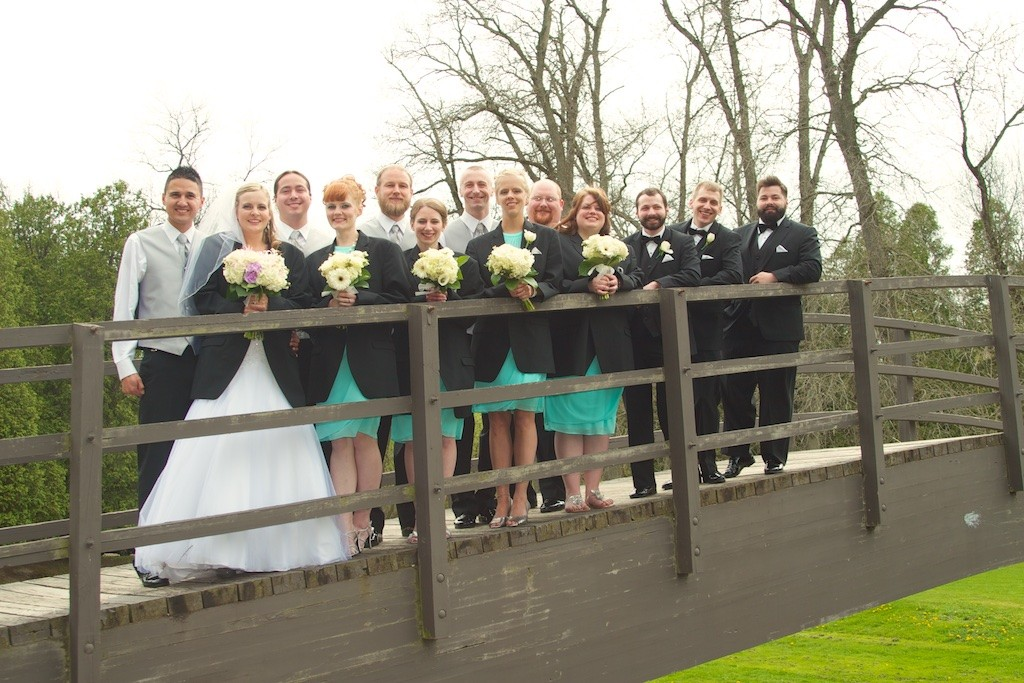 Groom and Bride with their Wedding Party on a Bridge in Evergreen Park, Sheboygan, WI Holding Flowers for their wedding day portraits