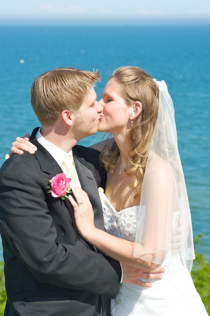 Groom Kissing Bride on the shore of Lake Michigan in Sheboygan, WI for their Wedding Day Portraits